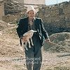 A shepherd tends to his lamb in Kosovo.