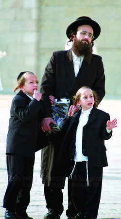 An Orthodox Jew and his sons contemplate at the Western Wall, also called the Wailing Wall. Many Jews feel closes to the destoryed temple here.