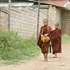As part of their rituals, novice male monks from Lashio walk through their village to get rice.