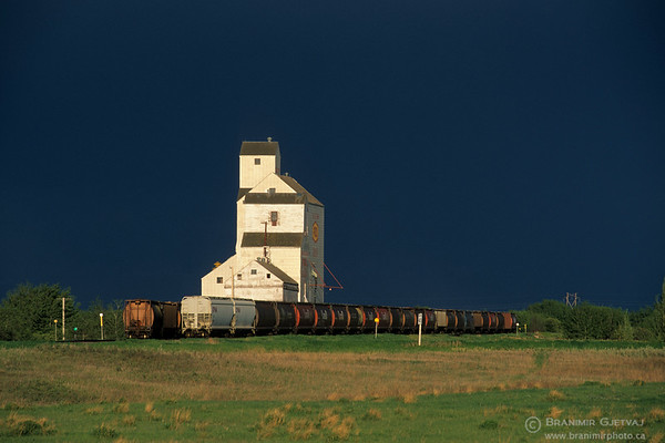 Grain elevator and freight train after a storm, Saskatchewan