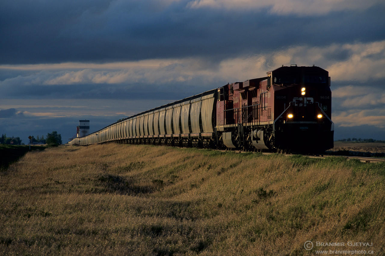 Freight train and grain elevator during storm, Saskatchewan