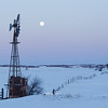 Windmill and moonrise over snow-covered fields. Saskatchewan