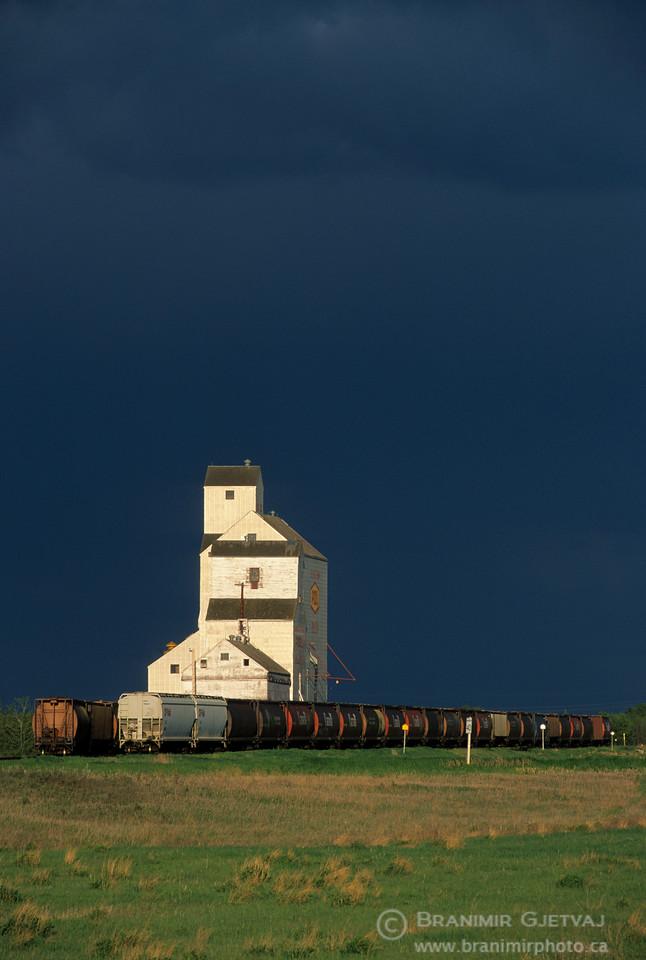 Grain elevator and freight train after a storm, Saskatchewan