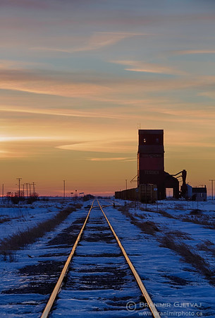 Grain elevator and train tracks at sunset, Saskatchewan