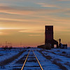 Grain elevator and train tracks at sunset, Saskatchewan