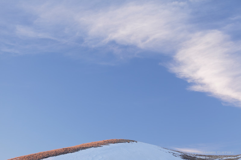 Cirrus cloud and snow-covered hillside (detail). Grasslands National Park