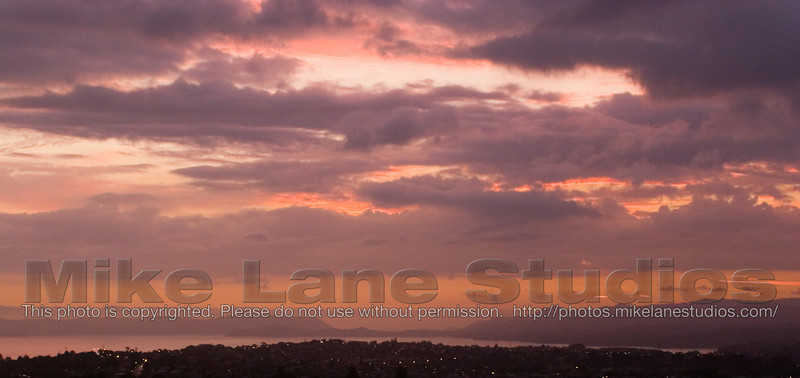 The sun sets over Auckland as viewed from the top of One Tree Hill.