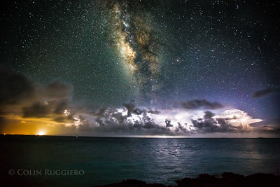 The Milky Way arcs through the night sky over a squall line on the horizon over Black Point Settlement in the Exuma Cays.