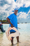 A local Bahamian stands with the jaws of a ten foot long bull shark that his brother killed with a bang stick.  these sharks are protected in the Bahamas but the laws are seldom enforced on  ...