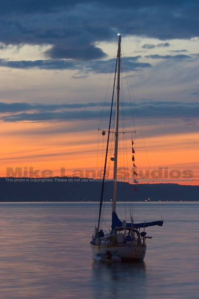 A sailboat anchored for the night in Commencement Bay.  Vashon Island is in the background.  Earlier this day the sky was completely overcast, by dusk the clouds had begun to part and the sky was vividly colored.