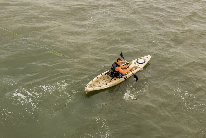 A guy in a kayak who took Shark Bait on fishing line way out into the water for the fishermen.
