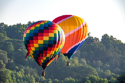 Pair of hot air balloons ascending above the mountains