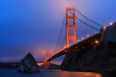 Low angle view of Golden Gate Bridge in fog at dusk