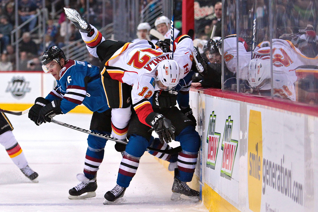 Calgary Flames right wing Jarome Iginla (12) gets up ended by Colorado Avalanche defenseman Ryan Wilson (44) and Colorado Avalanche center Paul Stastny (26) in the third period. The Colorado Avalanche won 2-1 in overtime. The Colorado Avalanche hosted the Calgary Flames at the Pepsi Center in Denver, CO.