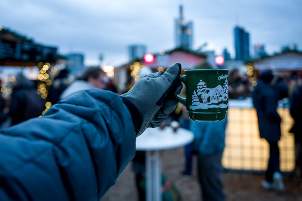 Frankfurt Christmas Market with spiced wine cup and Skyline in background.