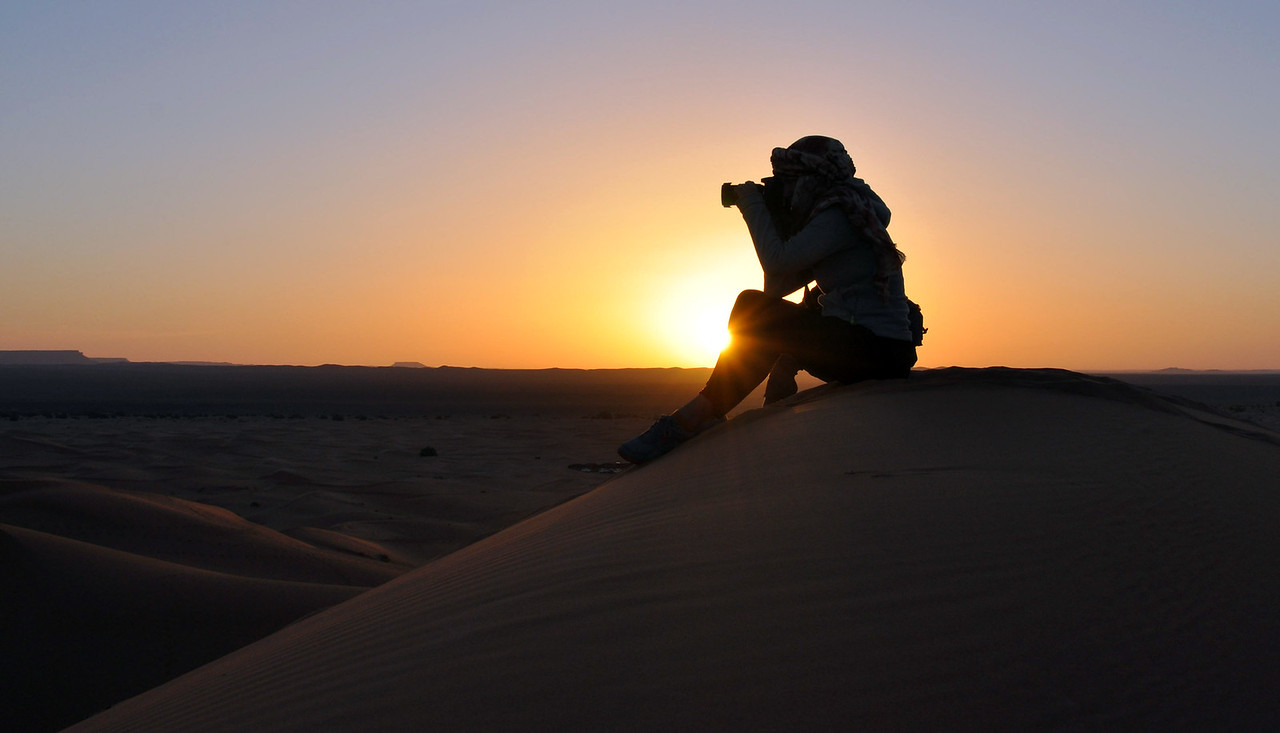 Taking photos in the dunes of the Sahara at sunrise