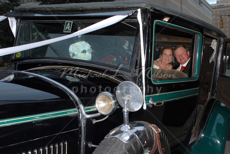 """<font size=4>Week 14  (Mike) -<br>""""Classy Couple"""" <font size=3> Everyone enjoys seeing Newlyweds in their """"Getaway Car."""" This Newlywed couple displayed an image of elegance as they made their getaway in this fully restored 1929 Hudson Super Six classic automobile.  I took this photo of Newlywed couple David and Darlene Holcomb as they arrived at the classy and elegant """"Tutwiler Hotel"""" in Birmingham, AL   <font size=4>To see more of this classy couples wedding photos click  <a href=""""http://mlnphoto.smugmug.com/gallery/5904760_9pS57"""">HERE </a>  ><font size=3> <br>Tech info: Aperture Priority mode, auto white balance, f8.0, at 1/60th second, Matrix Metering with Nikon SB 800 flash on TTL at ISO 400"""