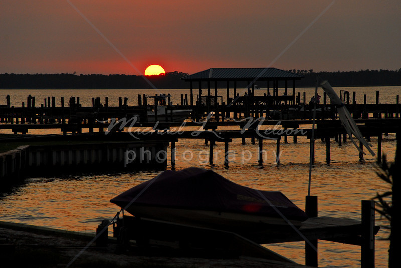 """font size=4>Week 46  (Mike) -<br> """"Wolf Bay Sunset"""" <font size=3> </i></b> Carol and I were blessed to watch the sun as it was setting over Wolf Bay on the Alabama Gulf Coast. Wolf Bay is part of the Perdido Bay inlet. I took this photo on the Orange Beach side of the bay.  <br>Tech info: Program mode, manual white balance,  f6.3, at 1/160th seconds. Multi Metering at ISO 320.  Colors, contrast, and levels adjusted in Photoshop Light Room 2 and Photoshop Elements."""