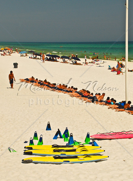 """font size=4>Week 49  (Mike) -<br> """"The Black Swimsuit Club"""" <font size=3> </i></b> Guys and girls line up on Fort Walton beach in their black swimsuits. They are not really members of a swimsuit club; they are taking part in a Lifeguard training program. In this photo they are waiting for the whistle blow signaling them to practice grabbing their gear and racing to the water as if someone were actually drowning.  <br>Tech info: Program mode, flash white balance,  f14, at 1/750th seconds. Photographed in custom Vivid mode w/ Multi Metering at ISO 320.  Colors, contrast, and levels adjusted in Photoshop Light Room 2 and Photoshop Elements."""