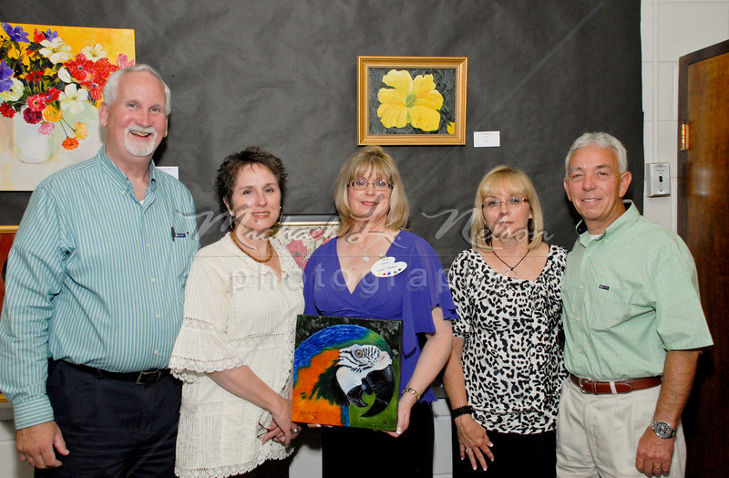 """<font size=4>Week 44  (Mike) -<br> """"Opening Night"""" <font size=3> </i></b> It was opening night for the talented artists of Lindart Studio, including my wife Carol.  Carol is shown in the center, with guests Joe & Debbie Tidwell (left side) and Jerry & Denise George (right side), as she holds her painting 'A Feathered Friend,'  with her painting 'Yellow Hibiscus' visible on the wall behind her. The exhibit was an impressive display of original artwork in oils, acrylics, and mixed media.  The artwork's quality and beauty absolutely dazzled the crowd at the Soon-Bok Lee Sellers Art Gallery in Hoover, AL. Opening night was fabulous with an attendance of more than 300 guests; however, if you missed it, you can still see the beautiful artwork on exhibit during the month of May. <br>Tech info: Manual mode, Auto white balance,  f5.6, at 1/125th seconds. Multi Metering at ISO 400.  Flash with Nikon SB 800 in TTL mode. Colors, contrast, and levels adjusted in Photoshop Light Room 2 and Photoshop Elements."""