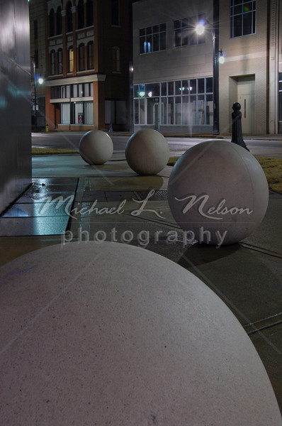 """<font size=4>Week 29  (Mike) -<br>""""Night Spheres"""" <font size=3> I have always liked night photography but I rarely get out and actually do much of it. On this particular night Carol and I spent about 2 hours taking photos on a on a rainy night in downtown Birmingham.  We got some nice photos, however I especially like this one. The concrete spheres, their shadows, the repetition of pattern, the perspective, and the reflectivity of the wet surfaces all combine to add interest to this shot. <font size =3> <br>Tech info: Aperture Priority mode, Auto white balance,  f16, at 2.2 seconds. Multi Metering at ISO 250. Edited and Cropped in Photoshop Elements"""