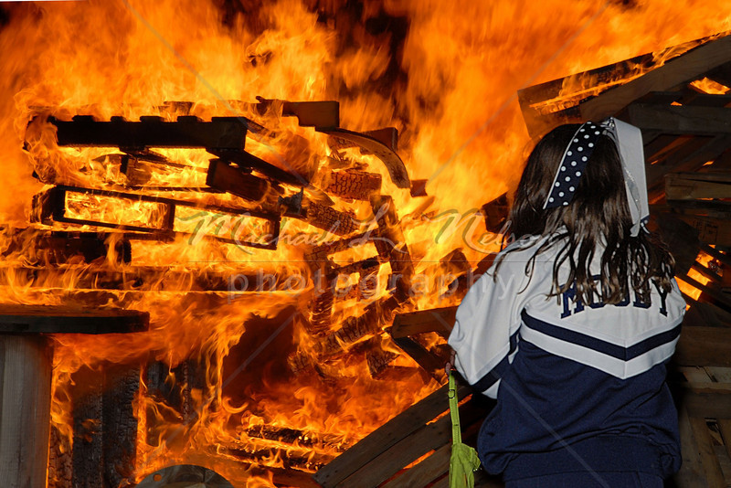 """<font size=4>Week 18  (Mike) -<br>""""Bonfire"""" <font size=3> It's Football season and everyone loves a bonfire. It was Homecoming night at Moody Park when this Junior Cheerleader caught my eye. She was completely dwarfed by the giant flames as she stood in fascination watching what was perhaps her 1st bonfire.  <br>Tech info: Manual mode, auto white balance,  f10.0, at 1/125th second using SB800 Flash. Multi Metering at ISO 200."""