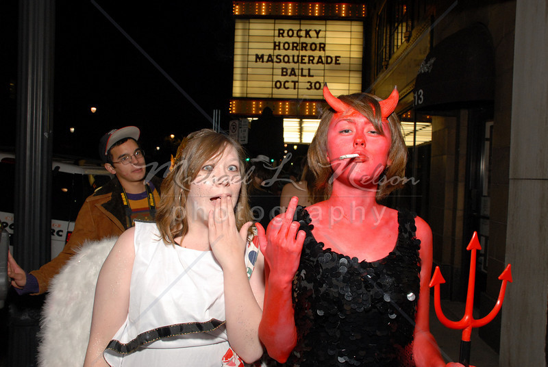 """<font size=4>Week 19  (Mike) -<br>""""Hand Signals"""" <font size=3> It's Halloween and everyone is in  costume. These two ladies dressed as an Angel and a Devil remain true to character in this photo taken in front of the Alabama Theatre. More than 1,500 people in costume attended the annual Rocky Horror Show and Masquerade Ball at the Alabama Theatre. <br>Tech info: Manual mode, flash white balance,  f6.3, at 1/100th second using Whale Tail diffuser on SB800 Flash. Multi Metering at ISO 400"""
