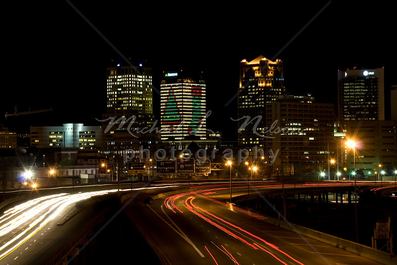 """<font size=4>Week 28  (Mike) -<br>""""Magic City Christmas"""" <font size=3> I have always thought that The Magic City has a beautiful skyline. Even though this is just a small section of the Birmingham skyline thousands of commuters see this portion everyday as they travel this section of interstate. Many of them are tired and exhaused from a long day at work and are frustrated at the traffic jams. However every December the Regions Bank Tower takes on this festive transformation that brings a smile to those commuters (including me) and reminds everyone passing by that It is Christmas Time.   <font size =3> <br>Tech info: Aperture Priority mode, Auto white balance,  f9, at 4.0 seconds. Multi Metering at ISO 200. Edited and Cropped in Photoshop Elements"""