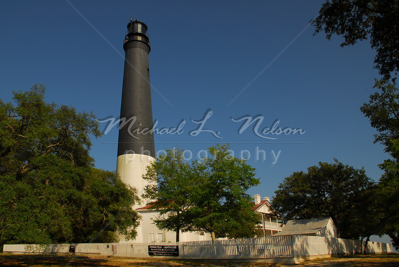 """font size=4>Week 48  (Mike) -<br> """"150 Year Old Beauty"""" <font size=3> </i></b> One of the few light houses still in operation, the Pensacola Light House located on the Naval Air Base in Pensacola, FL is celebrating it's birthday. The light house was first lighted on January 1, 1859. This light house is still using the original first order rotating Fresnel lens that flashes white every 20 seconds. The light house is 150 feet tall and is operated by the U.S. Coast Guard  <br>Tech info: Program mode, flash white balance,  f9.0, at 1/250th seconds. Photographed with a polarizer using Multi Metering at ISO 100.  Colors, contrast, and levels adjusted in Photoshop Light Room 2 and Photoshop Elements."""