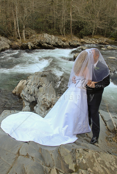 """<font size=4>Week 37  (Mike) -<br>""""Jason & Jerrica"""" <font size=3>What a gorgeous way to start your new life together. The photo of this Newlywed couple was taken in Gatlinburg, TN.  This beautiful river is located just off of Hwy. 321. Turn into the entrance of the Greenbriar Station of the National Park. The photo was taken on Saturday and it was 65 degrees. A cold front moved in and it snowed the next day (see that photo in week #36)  <font size =3> <br>Tech info: Manual mode, Auto white balance,  f10, at 1/15th seconds. Multi Metering at ISO 160.  Tripod mounted with fill flash from Nikon SB800. Contrast, and levels adjusted in Photoshop Light Room 2 and Photoshop Elements."""