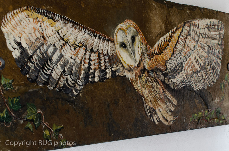 A painting of an owl on another huge thick slate slab.