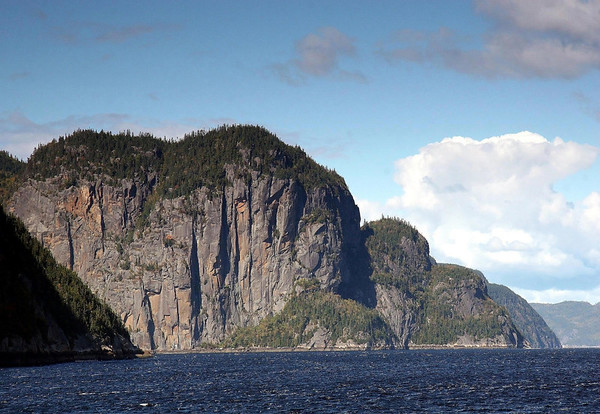 Beyond the partially shaded lower slope of Cape Eternity, across the mouth of the Eternity Bay, to Cape Trinity - along the Saguenay River - Saguenay Fjord National Park - Quebec