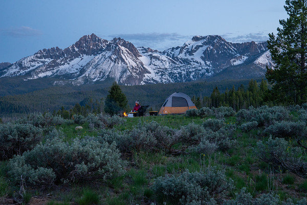 A warm fire beneath the snowy peaks of the Sawtooth in Idaho.