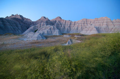 Prairie grass blows in the wind beneath the craggy ridges and spires in Badlands National Park in South Dakota.