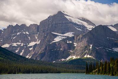 Cloud scraping peaks rise dramatically above Lake Josephine in Glacier National Park in Montana.