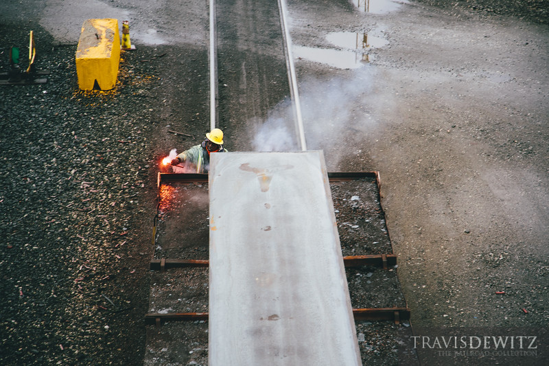 An Arcelor Mittal Steel employee lights a fusie as an end of train device before making a reverse movement of red hot slabs of steel.