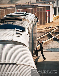 A worker on the ground climbs up to talk to the engineer before servicing the train.