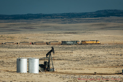 Oil jackpumps and their ajoining tanks dot the landscape all of the Powder River Basin along with strings of coal trains like this Union Pacific train heading south towards Douglas, Wyoming.