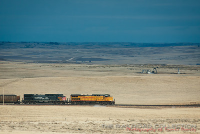 A Union Pacific coal train heads south of Bill, Wyoming across the Powder River Basin as an oil jackpump rocks off in the distance.