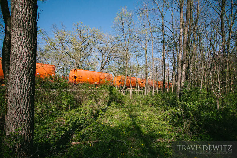 Wisconsin and Southern train of orange CRDX ballast hoppers roll through the woods near Edgerton, Wisconsin.