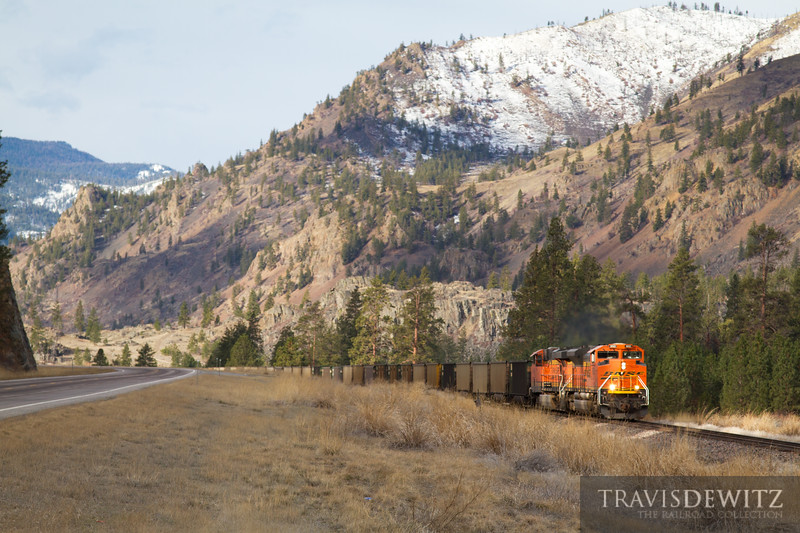A BNSF Railway coal train travels east through Perma, Montana along Highway 200.