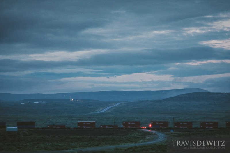 Red K-Line contains blur through a dirt road crossing as they head across Wyoming to the west coast.