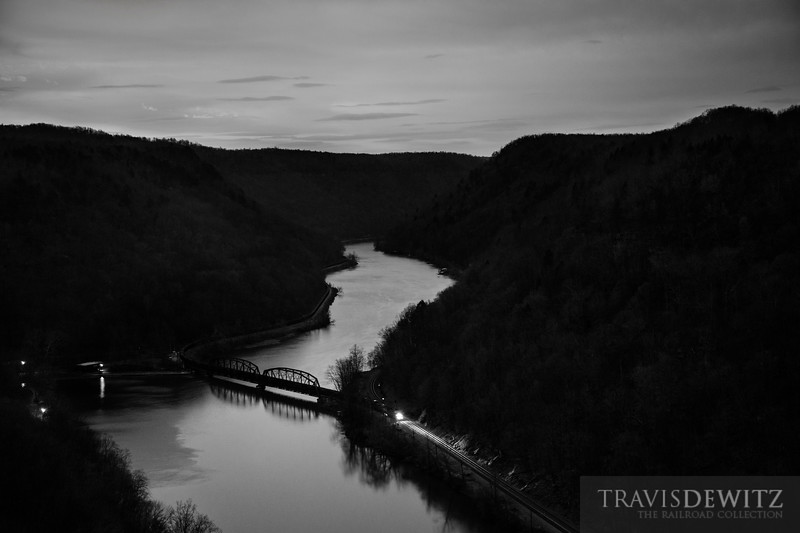 A CSX coal train lights a path along the dark gorge sides as it glids along the New River at just before sunrise.
