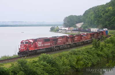 A Soo Line SD60 leads a string of red Canadian Pacific GEs up the Mississippi River at Maple Springs, Minnesota.  Travis Dewitz The Railroad Collection