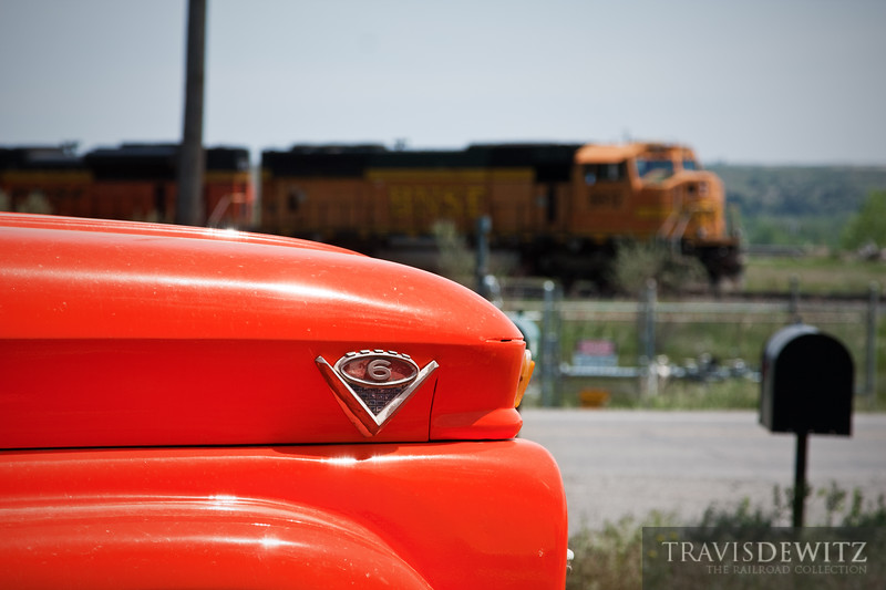 "A classic orange Chevrolet truck stands guard of this dirt drive just outside  Laurel, Montana while a BNSF freight sits and waits along the road for the Montana Rail Link's dispatcher to give them some trackage.  Travis Dewitz <a href=""http://www.therailroadcollection.com/latest-works/"" target=""_blank"">The Railroad Collection</a>"