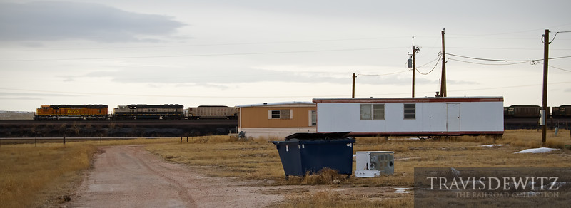 """A scene that can be found all across America, living on the wrong side of the tracks. A trailer court in despair with empty lots and dryer just laying skewed on the ground. The money heads down the rails as it leaves teh Powder River Basin and Bill, Wyoming behind.  Travis Dewitz <a href=""""http://www.therailroadcollection.com/latest-works/"""" target=""""_blank"""">The Railroad Collection</a>"""