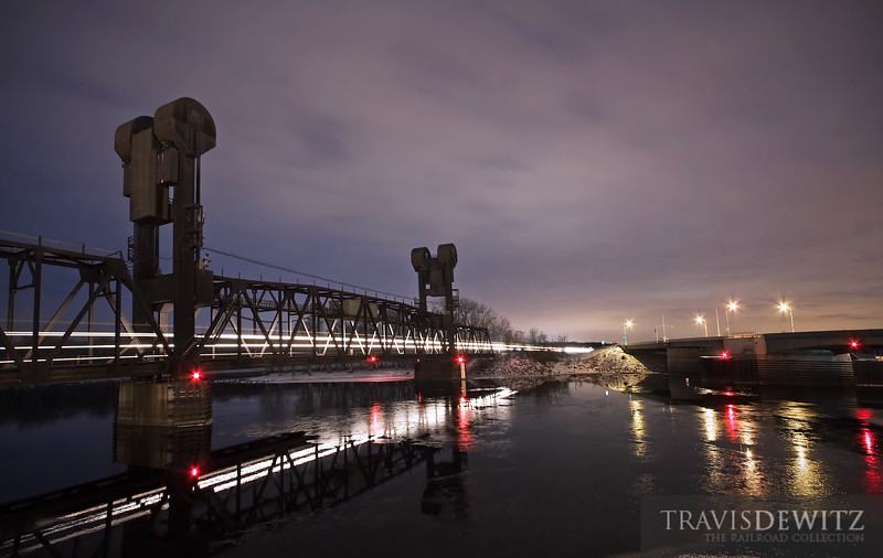 """A BNSF freight train streaks across the calm St. Croix River on the Prescott, Wisconsin lift bridge.  Travis Dewitz <a href=""""http://www.therailroadcollection.com/latest-works/"""" target=""""_blank"""">The Railroad Collection</a>"""