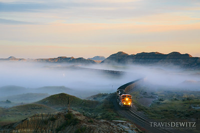 One of the most popular places to photograph trains in North Dakota is from this hill in the Bad Lands. The story behind this photo is a little more involved than I walked up the hill and waited for a train. The sun has just cracked the surface of the earth and the fog is beginning to lift quickly. I heard the train loudly approaching from the west as I pulled up. I quickly but cautiously ran to the base of the hill. Being from Wisconsin, rattlesnakes were on my mind and this particular area seems like a prime habitat. I could feel the train as it was about to emerge into view. I started up the steep side as quickly as possible before I realized the rain from the night before had turned the sides into a clay like slick mud. I almost landed face first but was able to catch myself. I still tried to quickly get up the hill as the train came into view. I thought about stopping and shooting the train from the lower plateau but the view wasn't what I wanted as I needed to get higher above the fog layer. Finding just a few rocky areas for footing I was able to reach the top as I carefully crossed the muddy areas making sure I didn't fall down either side as I scurred along the thin flat stretch near the top. I made it with impeccable timing to capture the frames I wanted. As the train continued past, the fog lifted quickly with a majority of it gone before the last coal cars went by. As I went to work my way back down, over an inch of mud was stuck to the bottom of my shoes. I was pretty sure the walk back down that mud slide wasn't going to go in my favor but I made it with no broken bones.