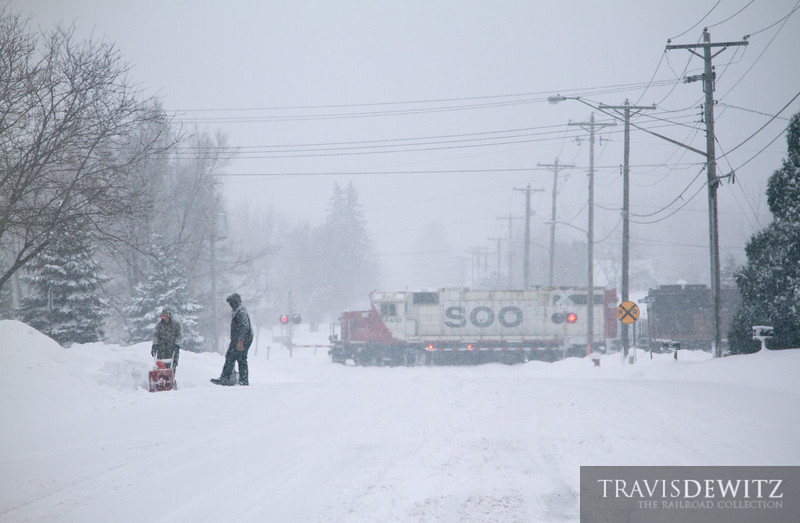 """Soo Line 4410 leads the local through a blizzard of snow as it heads down the yard track to the Wabasha, Minnesota yard office. Local residents try to keep up with the snowfall as the snowblow during the strom.  Travis Dewitz <a href=""""http://www.therailroadcollection.com/latest-works/"""" target=""""_blank"""">The Railroad Collection</a>"""