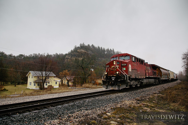 A westbound Canadian Pacific freight train led by just a single unit flies through Camp Douglas, Wisconsin underneath Target Bluff.